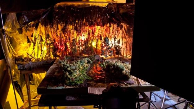 Diorama terbuat dari kayu, lumut, glitter kuning, kantong sampah transparan, gula masak, sikat botol, pasir, ubin grout yang di beri pewarna, kawat, kertas dan lampu kuning, merah, dan oranye.