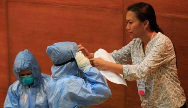 "Cegah Ebola, RSUD Madiun Siapkan 15 Alat Pelindung Petugas kesehatan membantu rekannya mengenakan baju pelindung dan peralatan di pelatihan ""One Nation, One Direction Pencegahan Ebola"", di Institut Penelitian untuk rumah sakit Tropical Medicine, Muntinlupa, Manila, Filipina, 28 Oktober 2014. (REUTERS/Romeo Ranoco)"