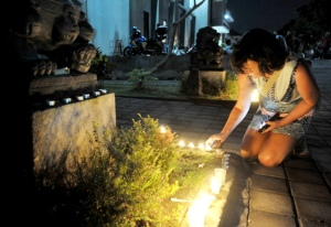 """Seorang relawan """"Mercy Campaign"""" menyalakan lilin di depan pintu penjara menjelang proses pemindahan dua warga Australia terpidana mati, Myuran Sukumaran dan Andrew Chan di Lapas Kerobokan, Denpasar, Rabu (4/3). Kedua terpidana mati dalam kasus penyelundupan narkoba tersebut dipindahkan ke Nusakambangan, Jawa Tengah untuk dieksekusi mati bersama 9 terpidana mati lainnya. ANTARA FOTO/Nyoman Budhiana/"""